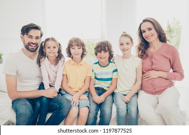 Big nice beautiful adorable adoptive lovely cheerful excited caucasian family in casual wear, six people, pregnant mum, bearded daddy, four children sitting in living-room, white light interior