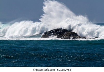 Big Ocean wave splashing on the Rocks near Waimea Bay on the north shore of Oahu Hawaii