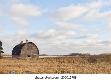 Big old barn with arched roof in rural autumn landscape