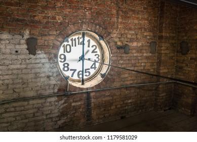 Big old clock embeded at the brick wall