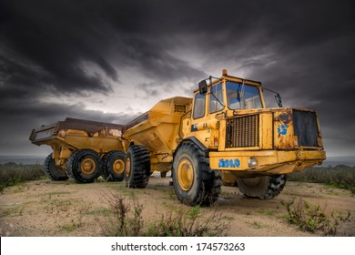 Big and old construction truck with a dark cloudy sky