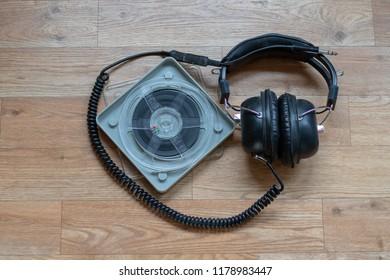 Big old headphones beside a single film roll