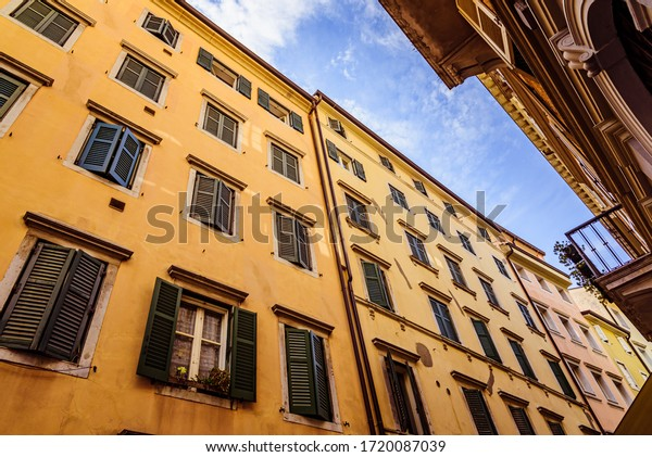 Big old yeloow building in italian style with closed green shutters on the windows