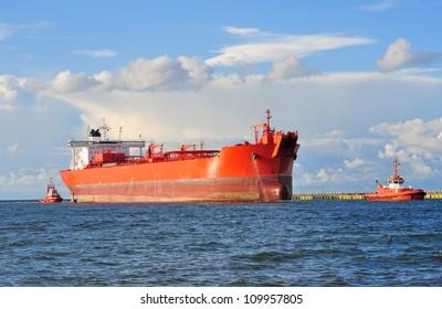 Big orange cargo ship heading for port