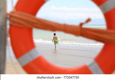 big orange life-buoy with the rescue rope and a young woman on the beach