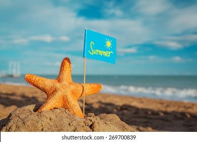 big orange starfish with flag at the seashore. Summer concept.