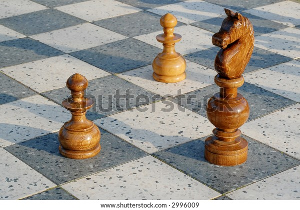 big outdoor chess game with wooden pawns
