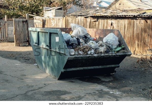 Big overfilled  trash dumpster in ghetto (Astrakhan, Russia)