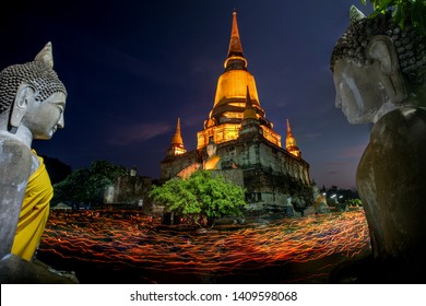 The big pagoda statue at twilight in Visakha Bucha Day, the buddhists pray and people walking with lighted candles in hand around a ancient temple of Thailand at Wat Yai Chai Mongkhon, Ayutthaya