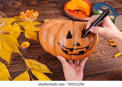 A big painted halloween pumpkin with leaves on a wooden background. Halloween concept