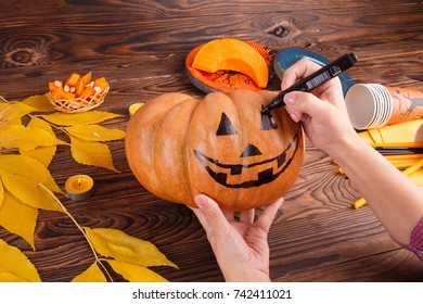 A big painted halloween pumpkin with leaves on a blue background. Halloween concept