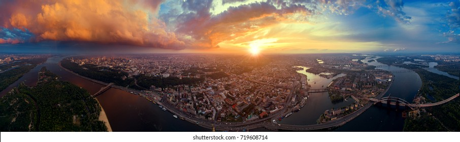 A big panorama of the city of Kiev on Podol at sunset. A modern metropolis in the center of Europe against the backdrop of a dramatic orange sky from a bird's eye view. Aerial view