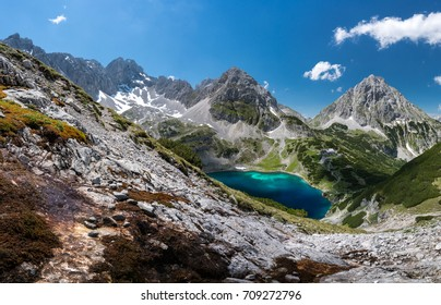 Big Panorama of a mountain lake surrounded by mountains during day time, sun and blue sky