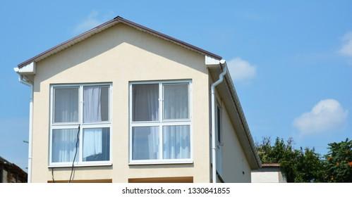 Big panoramic mansard house skylight windows photo. Attic skylight window wall. Building Modern House Construction with metal roof, rain gutter system.