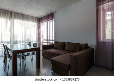 big panoramic windows with curtains and day light in dining room minimalistic interior with sofa and wooden table