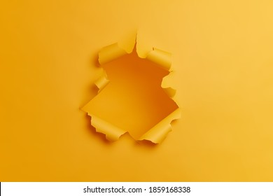 Big paper hole in center of yellow background. Blank space to insert your advertising content promotion or text information. Torn ripped studio wall. Breakthrough concept. No people in shot.