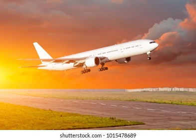 Big passenger airplane take off at sunset clouds on a runway