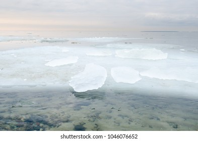 big pieces of broken ice on a Baltic sea in Estonia at sunset