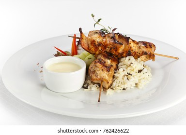 big pieces of grilled chicken, garnished with rice and sauce on plate