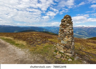 Big pile of Cairn on top of mountain at Kronplatz, with view of mountain range and blue sky, South Tyrol, Italy