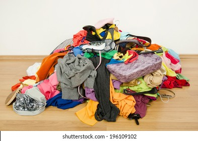 Big pile of clothes and accessories thrown on the ground. Untidy cluttered woman wardrobe all on the floor.