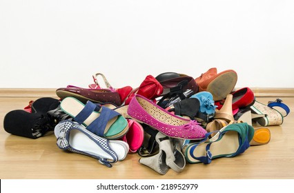 Big pile of colorful woman shoes. Untidy stack of shoes thrown on the ground.