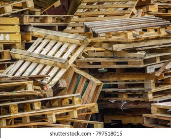 A big pile of used/grunge wood pallets placed randomly and dumped in an outdoor area. Old scrapped wooden shipping pallets in a jumbled pile.