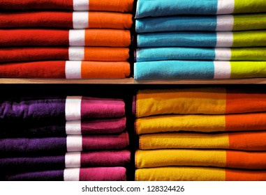 Big piles of colorful towels on the shelf