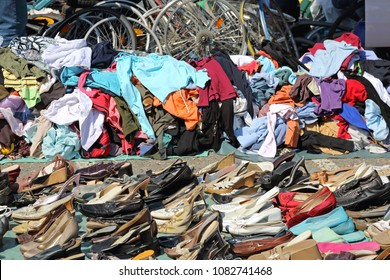 Big Piles of Second Hand Clothing and Shoes at Flea Market
