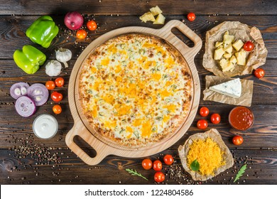 Big pizza with three kinds of cheese on a round cutting board on a dark wooden background. Ingredients.