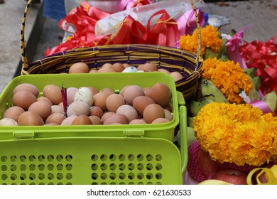 big plastic and bamboo baskets, fruits, boiled eggs and Marigold garlands on the table as token of redeeming a vow to the sacred Buddha image in the temple during Songkran festival