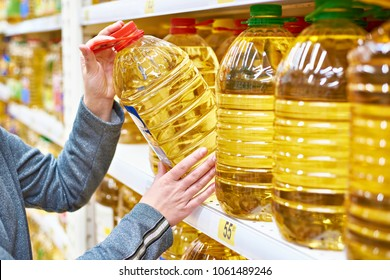 Big plastic bottle of olive oil in the hand of the buyer at the grocery store