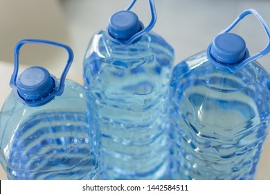 Big plastic bottle with water on the table over bright kitchen backgroung. Bottle of clear transarent water in a blue color cap and handle closeup.