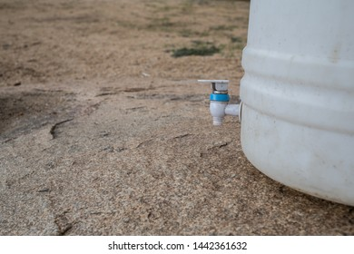 A big plastic water container with a tap on the ground in afternoon light.