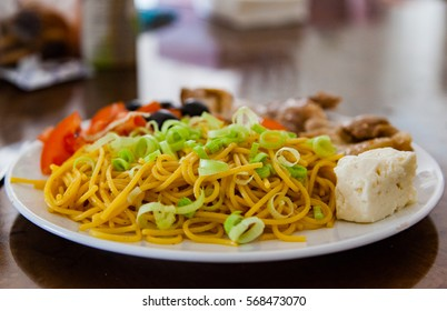 Big plate of spagetti with leek, tomatoes, olives and chicken looks like very delicious and healthy food