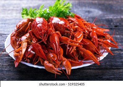 Big plate of tasty boiled crawfish closeup on wooden table, seafood dinner, nobody