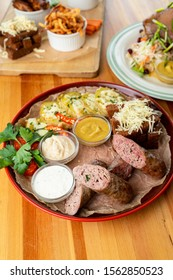 Big platter with beer snacks: sausage wurst, mustard, potato and croutons on wooden table