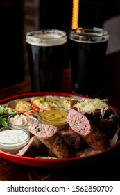Big platter with beer snacks: sausage wurst, mustard, potato and croutons served with two glasses of dark beer
