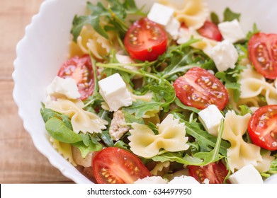 Big portion of homemade pasta salad with red cherry tomatoes, feta cheese, chicken breast, baby spinach leaves, arugula (rocket leaves) and farfalle. Appetizer. Healthy eating