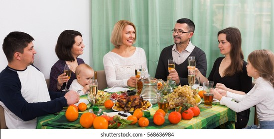 Big positive family sitting at holiday table, toasting and smiling