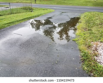 big puddle in asphalt driveway