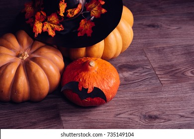 big pumpkin for halloween, black witch hat decorated with autumn golden leaves on a black background