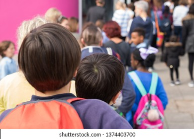 Big queue of parents and children near to school entrance. It`s an Open Doors Day in a School. Focus is on the one boy's head back in the queue. Welcome to school!
