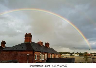 Big rainbow over a houses. cloudy sky