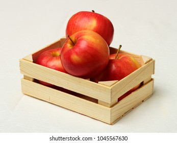 Big red apples in wooden box on white background.