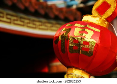 A big red Chinese lantern with a glittering golden word on it. The word means good fortune, happiness and blessings.