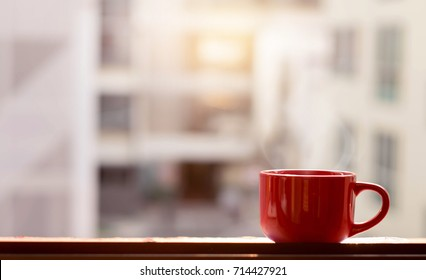 Big red cup with hot steam and sunlight at the window. Coffee and tea cup with smoke at glass window.