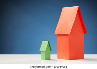 Big red paper house next to a small green one, on a white surface with a blue background.