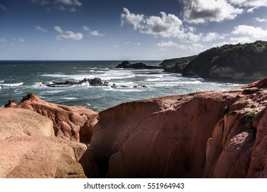 Big red rocks and the ocean with powerful waves and beautiful cloudy blue sky, rough water and rocks