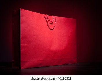 Big red shopping paper bag on dark red background